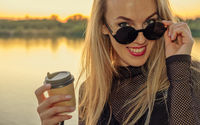 Closeup outdoor portrait of cute happy blonde Caucasian girl with takeaway coffee. Young woman with long hair wearing sunglasses in her 30s