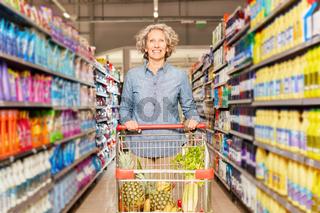Seniorin schiebt Einkaufswagen durch Supermarkt