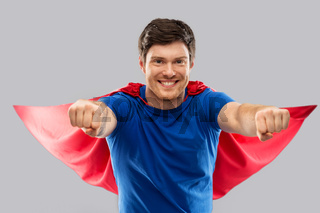 man in red superhero cape over grey background