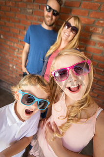 Cute Young Caucasian Brother And Sister Wearing Sunglasses with Parents Behind
