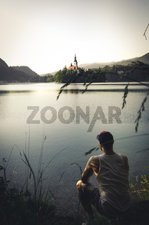 Travel Slovenia, Europe. Men looking on Bled Lake with Island, Castle and Alps Mountain on background.