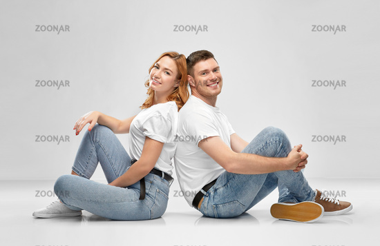happy couple in white t-shirts sitting on floor