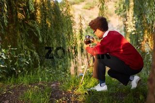Mann als Naturfotograf mit Kamera und Stativ