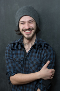 Portrait of a fashionable young man on dark background, chalkboard copyspace