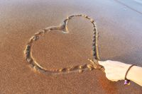 woman drawing a heart on the sand at sunset in a summer love concept.