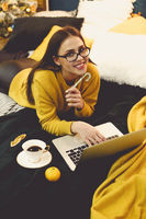 Beautiful young woman shopping online on laptop in cozy Christmas interior