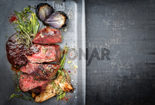 Modern Style Italian barbecue dry aged sliced chateaubriand with mushroom and onion as top view in a skillet with copy space right