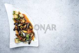 Traditional Italian blue mussel in white wine sauce as close up on a plate with copy space right