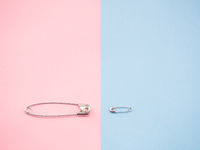 Two safety pins representing a man and a woman. Concept of machismo and feminism