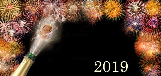 Champagnerflasche mit poppendem Korken vor Brillantfeuerwerk zu Neujahr 2019