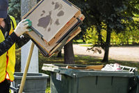 a janitor puts empty pizza boxes in a dumpster.