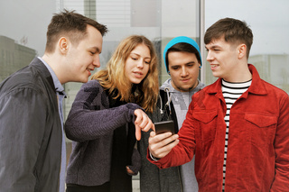 group of teenage friends having a discussion over some mobile phone content