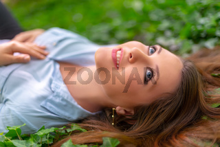 Young beautiful girl with perfect skin and makeup is lying down on ivy meadow, in spring park scenery, looking at the sky. Gorgeous woman outdoors enjoying nature. Healthy lady on green background