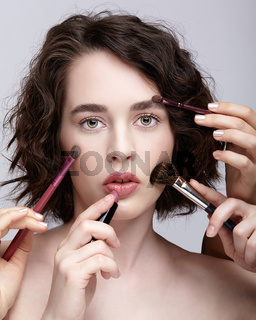 Make-up artist apply beauty makeup on the face of a beautiful girl. Visagist with makeup brush in hand