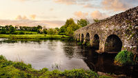 Old 12th century stone arch bridge over a river. Count Meath, Ireland