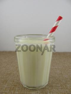 Frische selbstgemachte Buttermilch im Glas mit einem Strohhalm