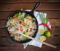 Frying pan with a dish of rice and vegetables on wooden table with lime, chili peppers and herbs