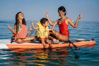 Mom and two little daughter doing yoga on the paddle board