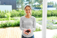 young woman with handful of soil at summer garden