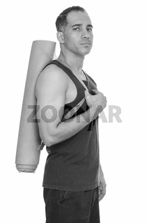 Mature handsome Persian man holding yoga mat getting ready for gym