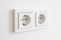 double socket, new electric plug on white wall -