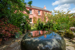 Small reflecting fountain and the pink cottage of the Dyffryn Fernant Garden