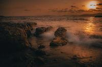 Steiniges Ufer am Meer bei Sonnenuntergang