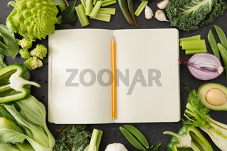 green vegetables and diary with empty pages