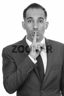 Mature handsome Persian businessman with finger on lips