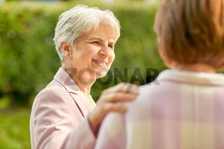 senior women or friends talking at summer park