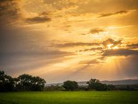 Sonnenuntergang mit dramatischen Wolken am Land