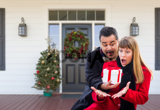 Young Mixed Race Couple Exchanging Gift On Front Porch of House with Christmas Decorations