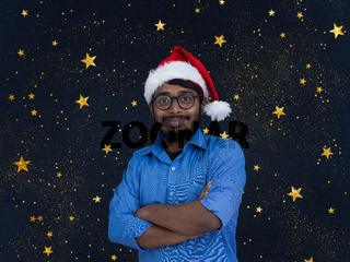 Indian man wearing traditional Santa Claus hat with stars in background