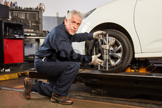Erfahrener KFZ Mechaniker macht eine Achsvermessung