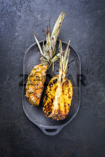Barbecue sliced pineapple as top view on a modern design cast iron pan with copy space
