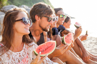 Friends eating watermelon on beach