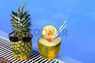 Pineapple wearing sunglasses and melon at pool