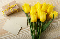Yellow tulips near blank greeting card and gift box on natural wooden background with space for text