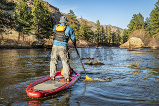 stand up paddling on mountain river