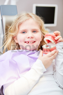 Mädchen als Patient zeigt Modell von Gebiss