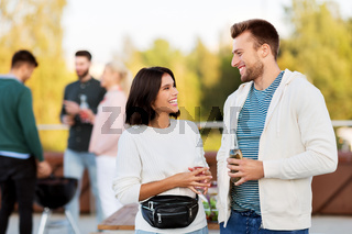 happy couple with drinks at rooftop party