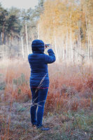 Woman taking photo of forest