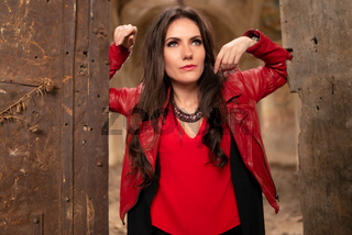 Fashion concept portrait of a gorgeous young woman in red leather jacket and black skirt outfit, sitting in a door of an old abandoned building and looking away. Body shot, retouched, vibrant colors
