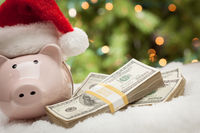 Piggy Bank Wearing Santa Hat Near Stacks of Hundred Dollar Bills on Snowflakes
