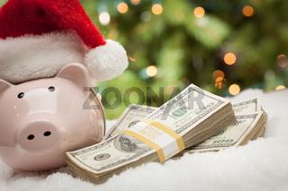 Piggy Bank Wearing Santa Hat Near Stacks of Hundred Dollar Bills on Snowflakes