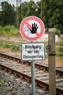 Schild warnt vor unbefugten Gleisübergang
