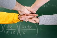Students putting hands together at the college with a blackboard in the background.