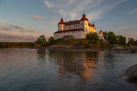 Last sun rays casting a warm light on Lacko castle with reflection in the waters of lake Vanern, Lidköping, Sweden