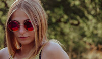 Attractive blond woman in trendy red sunglasses