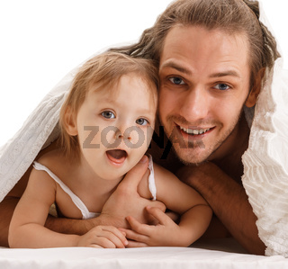 Handsome father and his small child lying in bed